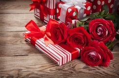 Roses et boîtes avec des cadeaux sur le vieux conseil photographie stock