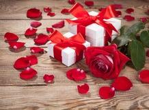 Roses et boîtiers blancs avec des cadeaux sur le vieux conseil photo libre de droits