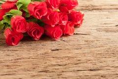 Roses et coeur rouge sur le vieux conseil en bois Images stock