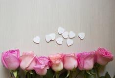 Roses et coeurs roses au-dessus de table en bois Fond de jour de valentines image stock