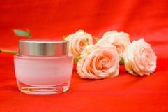 Roses et crème sur un fond rouge Image stock