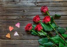 Roses et formes de coeur au-dessus de fond en bois Image stock