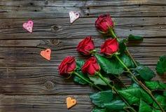 Roses et formes de coeur au-dessus de fond en bois Photos stock