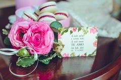 Roses et gâteau français de macaron Macarons colorés dans une boîte avec des fleurs à coté sur la table en bois Images stock