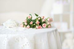 Roses et petits programmes roses sensibles de perle sur la table Photo stock