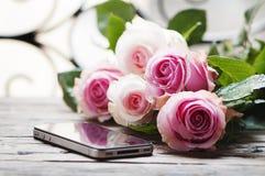 Roses et smartphone roses sur la table en bois Image libre de droits