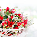 Roses fake  flower bouquet in white basket.  Royalty Free Stock Photos