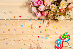 Roses flowers  with heart shape candy on wooden background Paste Stock Images