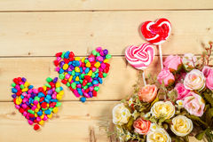 Roses flowers  with heart shape candy on wooden background Paste Royalty Free Stock Photo