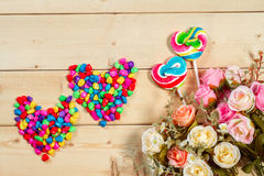 Roses flowers  with heart shape candy on wooden background Paste Stock Photos