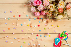 Roses flowers  with heart shape candy on wooden background Paste Stock Photography