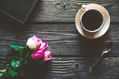 Roses fraîches avec le journal intime et la tasse de café sur la table en bois, vue supérieure fleurs, boisson chaude Images libres de droits