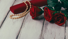 Roses and gift box with bead on wooden table. Valentines day concept. Copy space Royalty Free Stock Image