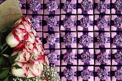 Roses and Gift Boxes Background. Flat lay of long stem pink and white roses over a background of violet color gift boxes with pretty bows Stock Images