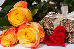 Roses with a gift and heart. Three roses with a gift and heart Stock Photo