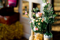 Roses in glass bottles. Pink roses in glass bottles decorated with burlap Stock Images