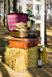 Roses in glass bottles. Pink roses in glass bottles decorated with burlap face on old suitcase with straw Stock Images