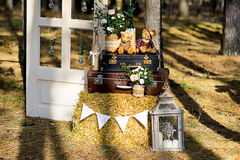 Roses in glass bottles. Pink roses in glass bottles decorated with burlap face on old suitcase with straw. Nearby sit two teddy bear Stock Photo