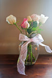 Roses in glass vase. With pink ribbon Stock Images