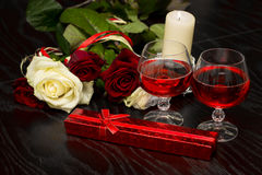 Roses, glasses of wine and a box with a jewel in the light of candles Stock Images