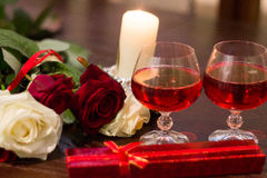 Roses, glasses of wine and a box with a jewel in the light of candles Royalty Free Stock Image