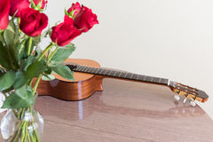 Roses and guitar lying on the table. Still life with a bouquet of roses and a guitar Royalty Free Stock Image