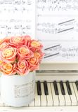 Beautiful pink roses in a round box on the piano. Roses in a Hat Box. Beautiful pink roses in a round box on the piano Royalty Free Stock Photos