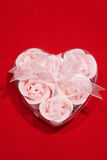 Roses in heart. Soap in the form of roses in a box in the form of heart on red background stock photos