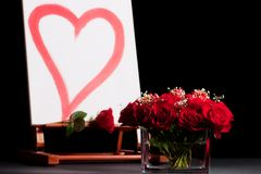 Roses and heart on easel. Studio still life of a red heart painted on canvas on a wooden easel with a dozen red roses in a short glass vase against a black royalty free stock photo