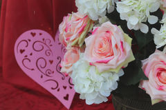 Roses and a heart. Pink heart and white and pink cloth roses with a red background Royalty Free Stock Images