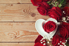 Roses with heart shape coffee cup on wooden background. View from above