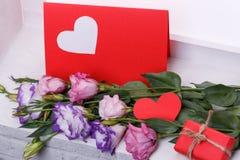 Roses japonaises à côté d'une carte postale avec un coeur et un petit cadeau sur un plan rapproché de filon-couche de fenêtre Image libre de droits