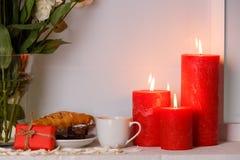 Roses japonaises dans un vase de l'eau à côté du petit déjeuner et des bougies brûlantes en gros plan sur un fenêtre-filon-couche Image stock