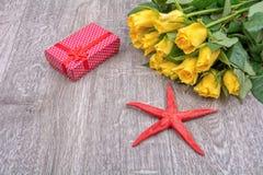 Roses jaunes, cadeau rouge et étoiles de mer rouges sur le fond en bois Photo libre de droits