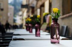 Roses jaunes dans bouteilles pourpres transparentes Photographie stock libre de droits