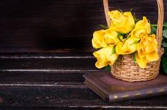 Roses jaunes dans un panier, livre de vintage sur le fond en bois L'espace libre pour votre texte Photo libre de droits