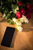 Roses jaunes et rouges avec le smartphone sur la table en bois Images libres de droits