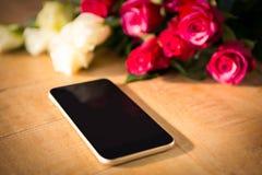 Roses jaunes et rouges avec le smartphone sur la table en bois Image stock