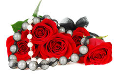Roses and jewelery. Beautiful red roses with black pearl jewelery isolated on the white stock photos