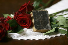Roses, lace and prayer book still life 1. Red roses on white lace and black book with cross Royalty Free Stock Photo