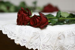 Roses and  lace still life 2. Two red roses on white lace vintage table-cloth Royalty Free Stock Images