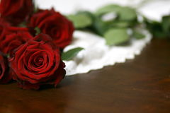 Roses and lace on table still life 4. Red roses on white lace on wooden table Royalty Free Stock Images