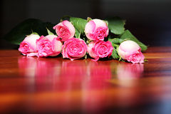 Roses laid on woodfloor with reflection. Dozen of long stem roses laid on a woodfloor Stock Photography