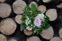 Roses - le bouquet se trouve entre le bois de chauffage Photo libre de droits