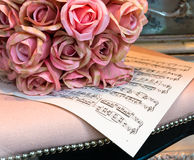 Roses and Music. Bunch of Silk Roses on Sheet of Music Royalty Free Stock Image