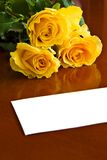 Roses with note. Three yellow roses on table with blank note stock images