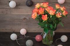 Roses oranges de floraison sur un fond et une guirlande en bois gris-clair sous forme de boules, enveloppées en fil coloré Image libre de droits