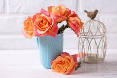 Roses oranges fraîches dans la bougie bleue d'american national standard de tasse sur le backg en bois blanc Photographie stock libre de droits