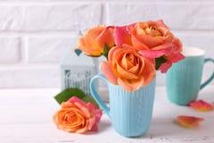 Roses oranges fraîches dans la tasse bleue Images libres de droits