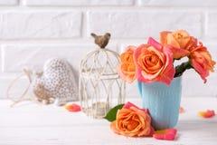 Roses oranges fraîches dans la tasse bleue, bougie d'american national standard de coeur sur le woode blanc Photo stock